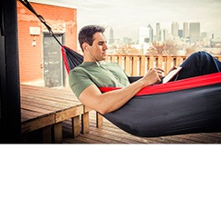 man laying in hammock with phone